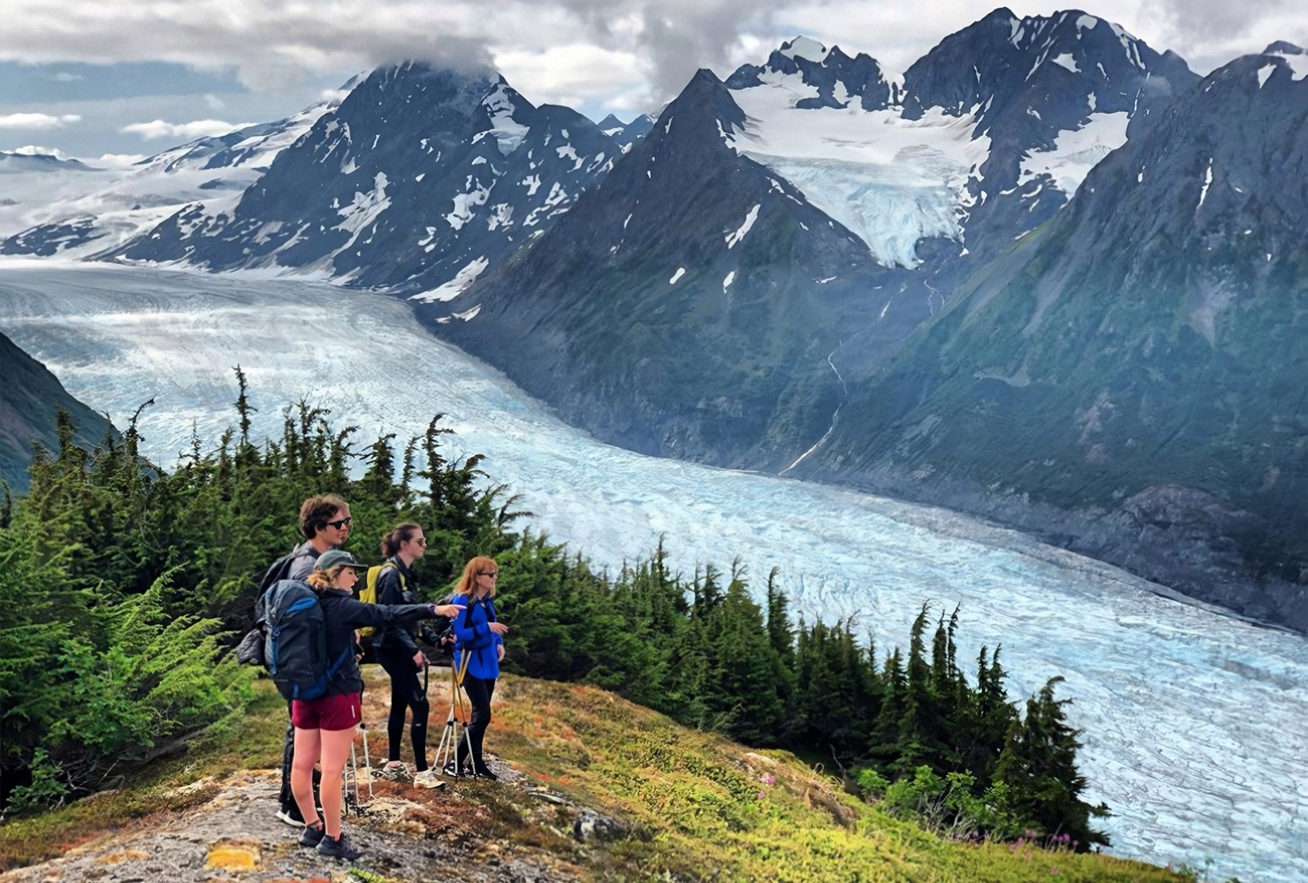 3 people viewing the Alaska outdoor scenery. They are in a grassy field overlooking water and snow peaked mountains.
